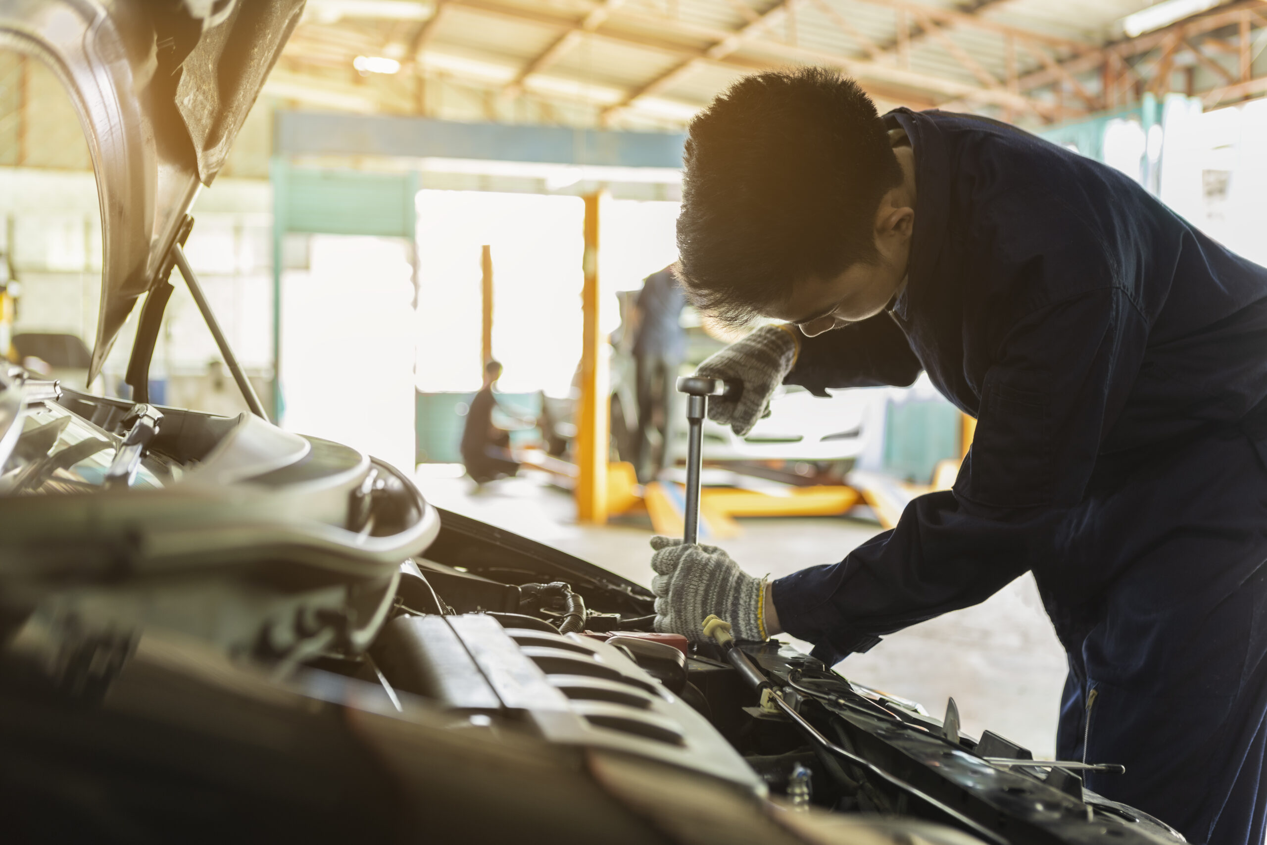 Asian man auto mechanic using a wrench and screwdriver to working service car in garage.